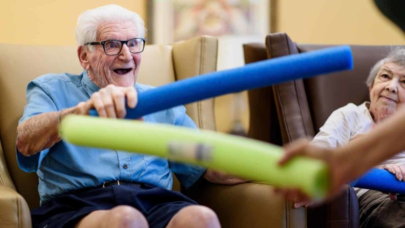 Senior man holding blue foam noodle during memory care therapeutic activity