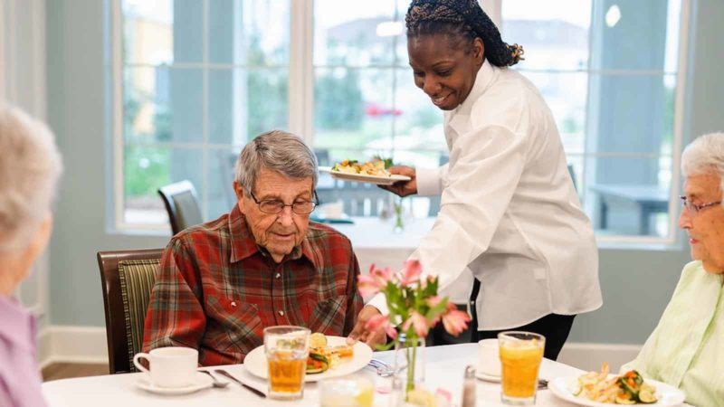 Senior man seated at dining table being served food by dining staff in memory care dining room