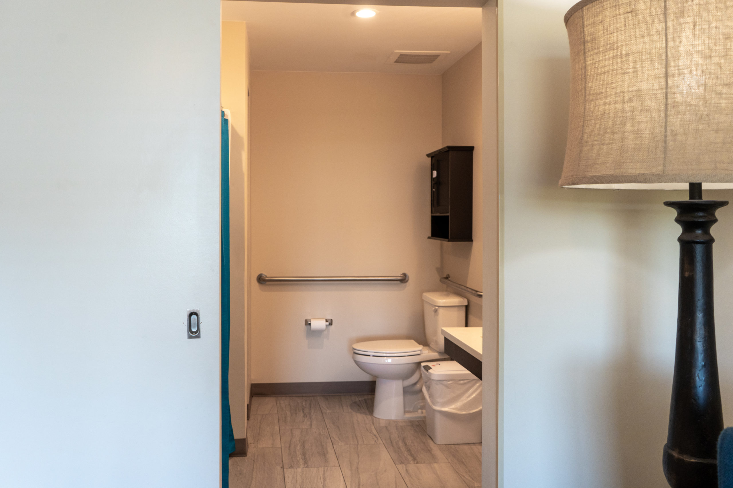 Private bathroom with toilet, sink and safety walk-in shower